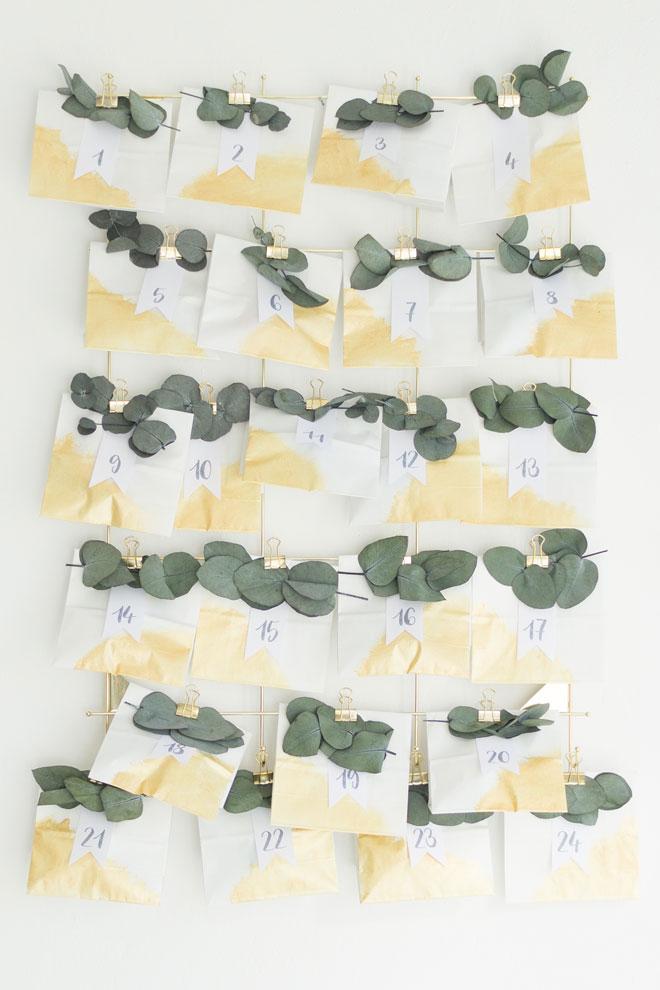 Adventskalender selber machen, DIY-Idee mit Eukalyptus und weiß-goldenen Papiertüten an der Wand angebracht