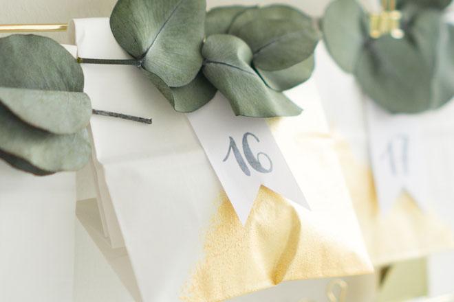 Adventskalender selber machen, weiß-goldene Papiertüte mit Eukalyptus und Zahlenfähnchen