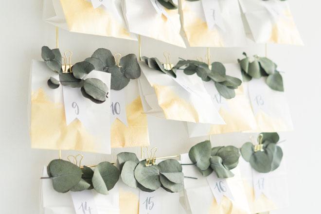 Adventskalender selber machen mit Eukalyptus auf weiß-goldenen Papiertüten