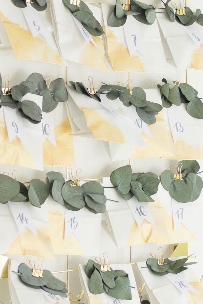 Adventskalender selber machen, DIY-Idee mit Eukalyptus und weiß-goldenen Papiertüten