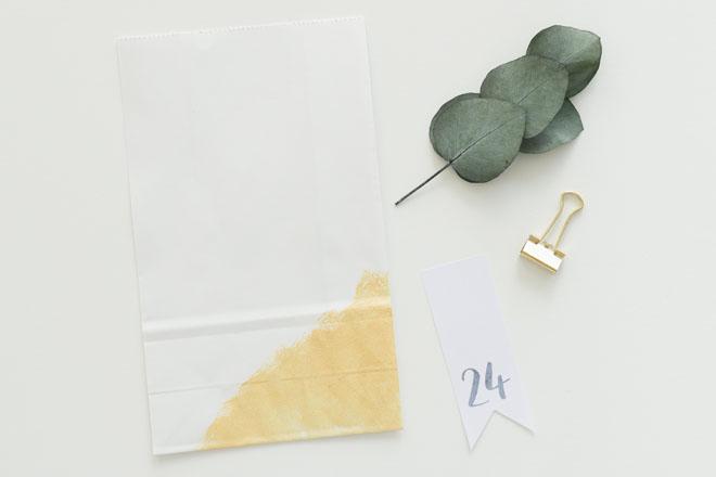 Adventskalender selber machen, vorbereitete weiß-goldene Papiertüte mit Eukalyptuszweig, Zahlenfähnchen und Foldback Klammer