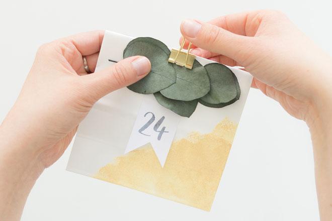 Adventskalender selber machen, Zahlenfähnchen und Eukalyptus an weiß-goldener Papiertüte mit Foldback Klammer befestigen