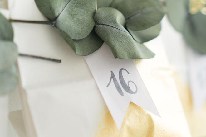 Adventskalender selber machen, befüllte weiß-goldene Papiertüte mit Zahlenfähnchen und Eukalyptus