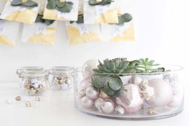 Deko-Idee moderne Weihnachtsdeko in der Glasschale mit Sukkulenten, Eukalyptus, rosé-farbenen Christbaumkugeln und Lucky Stars
