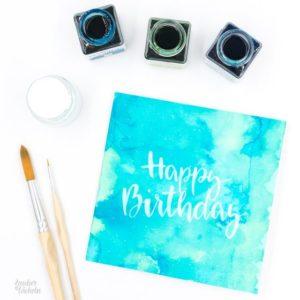 Geburtstagskarte Happy Birthday mit weißem Brushlettering auf Aquarellhintergrund von Zauber ein Lächeln.