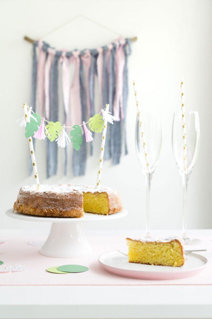 Kuchen dekorieren mit einem Cake Topper mit Quasten und tropischen Blättern